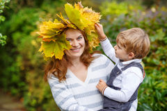 Young  mother in a maple leaf wreath holding little toddler boy. In autumn park Stock Photos