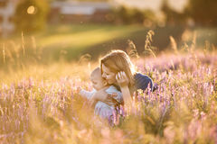 Young mother in nature with baby son in the arms. Beautiful young mother holding her little baby son in the arms outdoors in nature in lavender field stock images