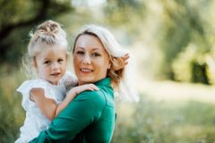 Young mother in nature holding small daughter in the arms. Copy space. Beautiful young mother in green sunny summer nature holding her cute small daughter in royalty free stock photos