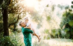 Young mother in nature holding small daughter in the arms in summer. Copy space. Beautiful young mother in green sunny summer nature holding her cute small stock photo