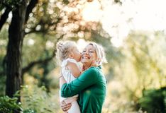 Young mother in nature with small daughter, kissing. Young mother with small daughter on a meadow in nature, kissing stock photos