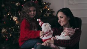 Young mother with a newborn baby and daughter near Christmas tree stock video