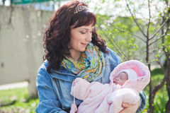 Young mother with newborn baby in outdoors at spring day Royalty Free Stock Photo