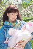 Young mother with newborn baby in outdoors at spring day Stock Image