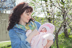 Young mother with newborn baby in outdoors at spring day Stock Photography