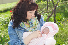Young mother with newborn baby in outdoors at spring day Royalty Free Stock Images
