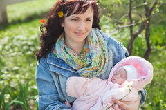Young mother with newborn baby in outdoors at spring day Royalty Free Stock Photography