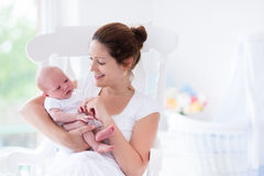 Young mother and newborn baby in white bedroom Royalty Free Stock Images