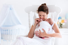 Young mother and newborn baby in white bedroom Stock Image