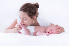 Young mother and newborn baby in white bedroom Stock Photos