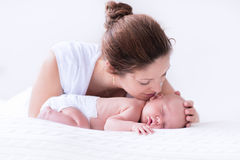 Young mother and newborn baby in white bedroom Royalty Free Stock Image