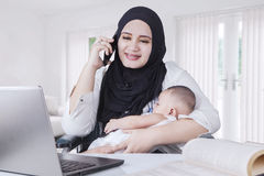 Young Mother Nursing her Baby while Working Stock Photography