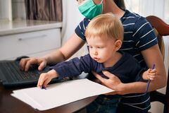 Free Young Mother On Maternity Leave Trying To Freelance By The Desk With Toddler Child. Stock Photo - 181359880