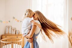 Free Young Mother Or Babysitter With A Little Girl In Her Arms Spin In The Middle Of The Room Stock Image - 187031371