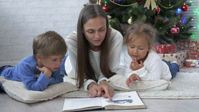 Young mother other with two kids reading a book on the floor near Christmas tree stock footage