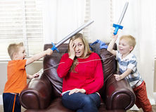Young Mother overwhelmed by her kids Stock Image