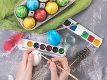 Young mother painting Easter eggs stock photography