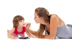 Young mother paints lipstick little daughter Royalty Free Stock Images