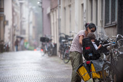 Young mother places her child on bike in the rain. Amsterdam Royalty Free Stock Image