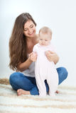 Young mother playing with baby on carpet Royalty Free Stock Photo