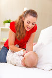 Young mother playing with baby on divan Stock Photography