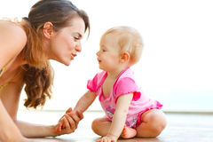 Young mother playing with baby on floor Royalty Free Stock Photography