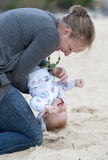 Young Mother playing with baby on the sand Royalty Free Stock Photo