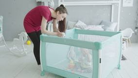 Young mother playing with baby sitting in playpen stock video