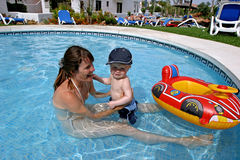 Young mother playing in children's swimming pool with toddler son and inflatable boat.
