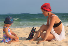 Young mother playing with daughter on beach Royalty Free Stock Images