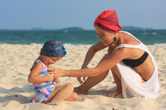 Young mother playing with daughter on beach Stock Photo