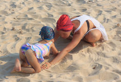 Young mother playing with daughter on beach Stock Image