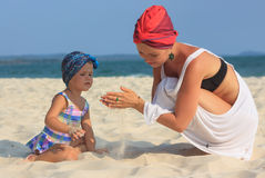 Young mother playing with daughter on beach Stock Photography