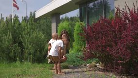 Young mother playing and having fun with her baby boy son brothers in a green garden - family values warm color summer. Scene - white caucasian parent stock footage