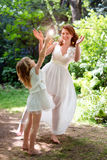 Young mother playing and having fun with her little daughter in green summer park. Family happiness, childhood concept. Royalty Free Stock Photo