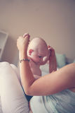 Young mother playing with her baby boy in bed. Stock Image