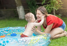 Young mother playing with her baby boy in inflatable swimming po. Happy young mother playing with her baby boy in inflatable swimming pool Stock Photography