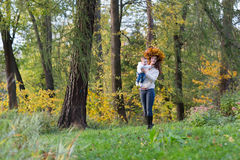 Young mother playing with her baby daughter in an autumn park Stock Photos