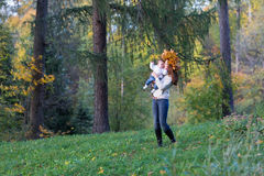 Young mother playing with her baby daughter in an autumn park Royalty Free Stock Image