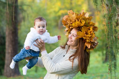 Young mother playing with her baby daughter in an autumn park. Wearing a maple leaf wreath Stock Photo