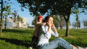 Young mother playing with her baby in the park. Happy woman puts on the back of the child royalty free stock images