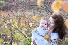 Young mother playing with her baby on a sunny autumn day Stock Photography