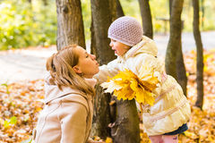 Young mother playing with her daughter in autumn park Stock Photos
