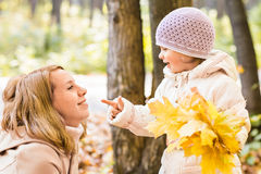 Young mother playing with her daughter in autumn park Royalty Free Stock Image