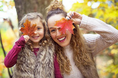 Young mother playing with her daughter in autumn park Stock Photo