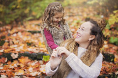 Young mother playing with her daughter in autumn park Stock Image