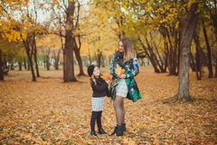 Young mother playing with her daughter in autumn park royalty free stock photo