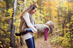 Young mother playing with her daughter in autumn park Stock Images