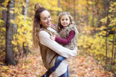 Young mother playing with her daughter in autumn park Royalty Free Stock Images