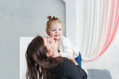Young mother playing with her little daughter and lift up the baby. royalty free stock photos